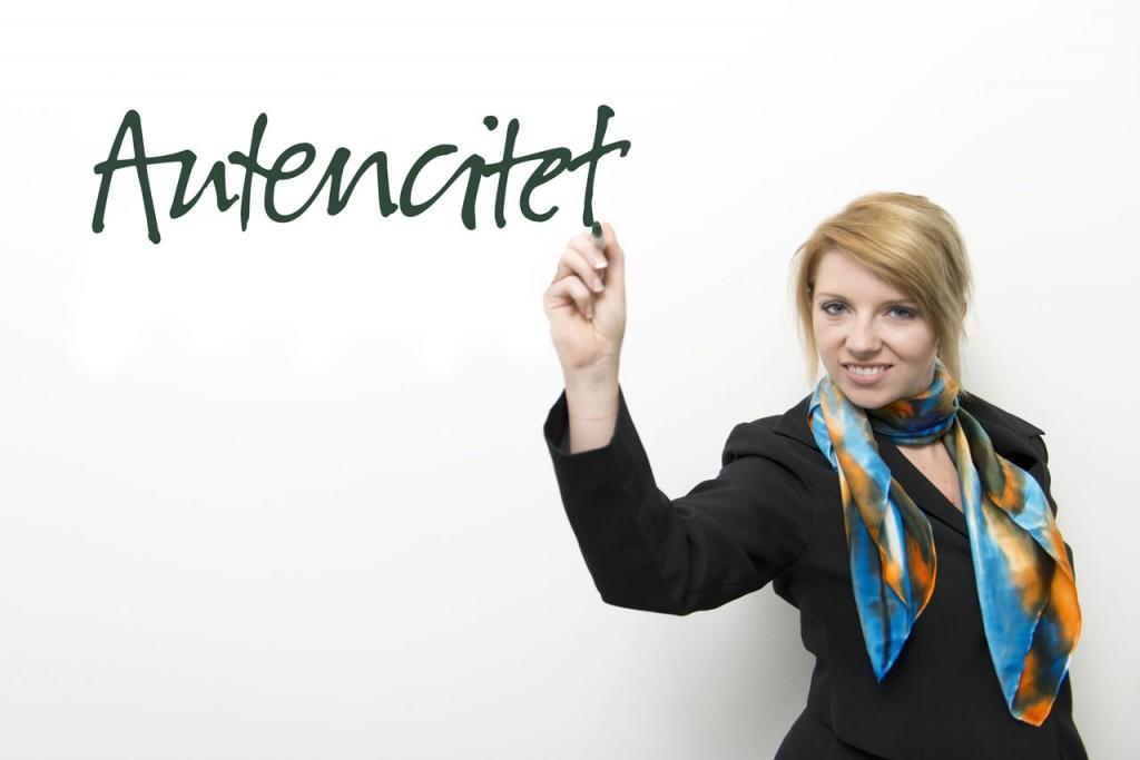 """Billede af konsulent, der har skrevet """"autencitet"""" (i stedet for """"autenticitet"""") på det whiteboard, hun står foran"""